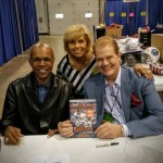 Gale Sayers and his wife with Chet Coppock and his new book at the 36th National.